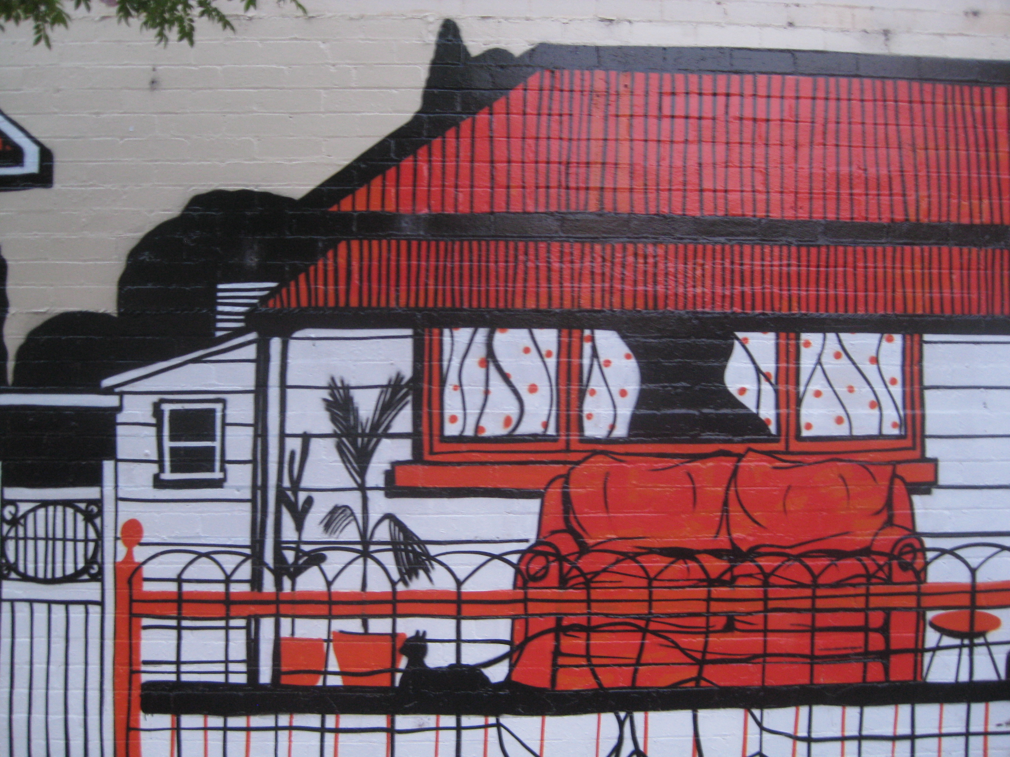 footscray graffiti orange black white house with a couch and cat on the porch
