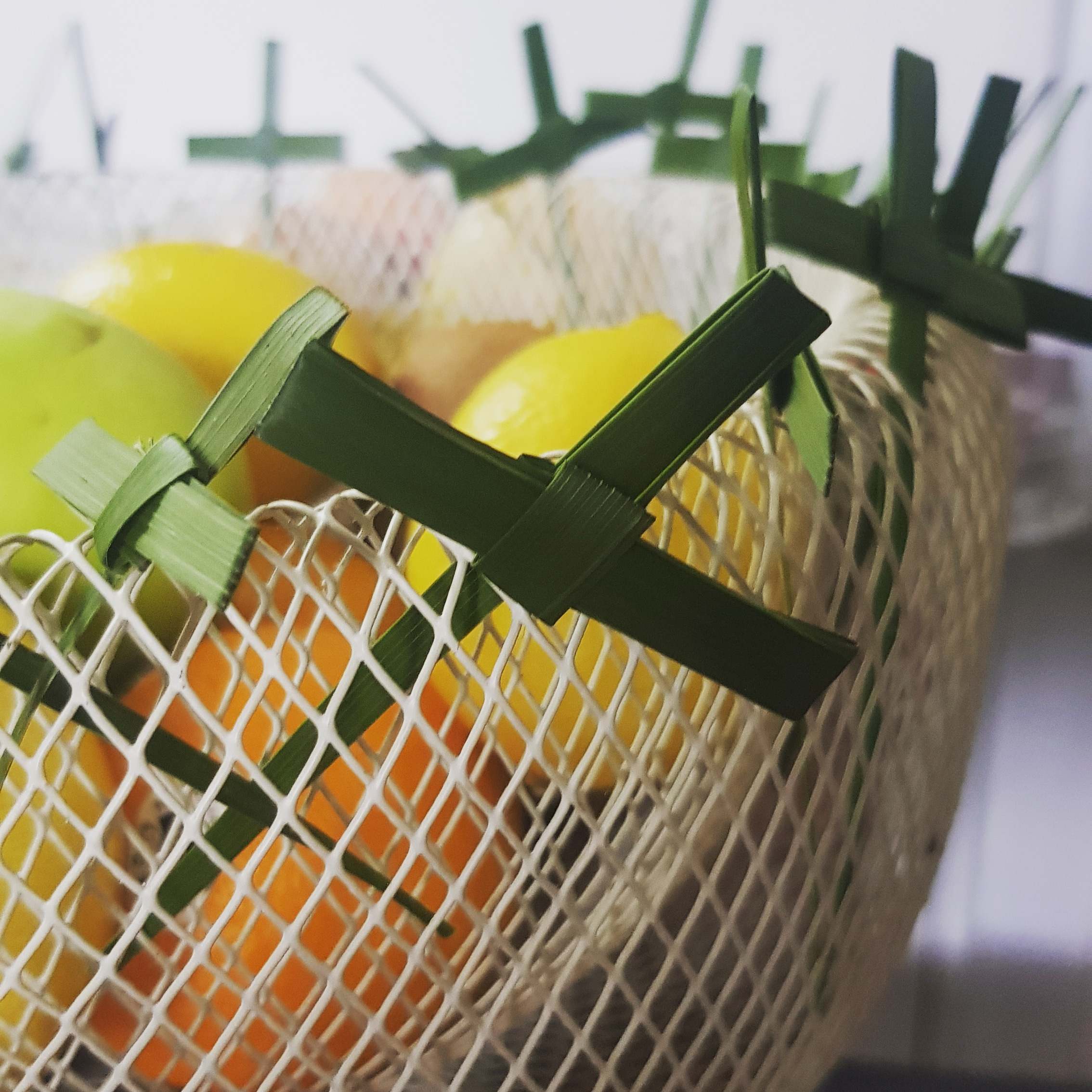 ash wednesday crosses are tucked into the edge of a mesh fruit bowl lent 2020